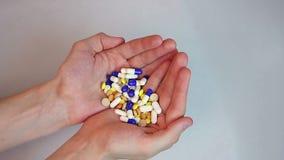 拿着两极少数五颜六色的片剂和胶囊的人 影视素材