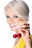 拿着两棵成熟樱桃的美丽的白肤金发的妇女 库存照片