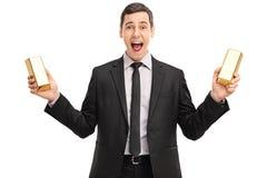 拿着两种金制马上的齿龈的激动的商人 免版税库存图片