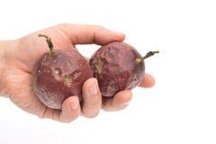 拿着两西番莲果的手 免版税库存图片