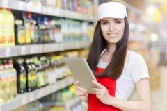 拿着个人计算机片剂的微笑的超级市场雇员 库存照片