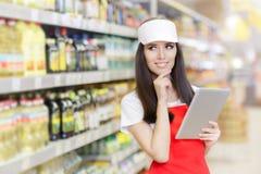 拿着个人计算机片剂的微笑的超级市场雇员 库存图片
