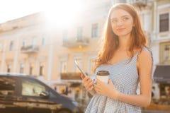 拿着个人计算机的微笑的偶然女孩压片和咖啡 免版税库存图片