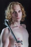 拿着中世纪武器的年轻白肤金发的人 图库摄影