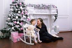 拿着中看不中用的物品的愉快的母亲和可爱的婴孩画象反对与圣诞树的国内欢乐背景 女孩 免版税图库摄影