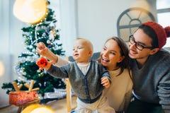 拿着中看不中用的物品的母亲、父亲和婴孩 图库摄影