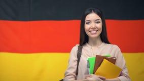 拿着习字簿的愉快的女生反对德国旗子背景,教育 股票视频