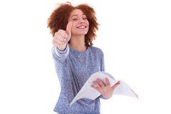 拿着书和做Th的黑人非裔美国人的学生女孩 免版税库存图片