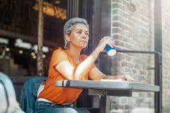 拿着书和喝咖啡的可爱的年轻白肤金发的女孩在咖啡馆 免版税库存图片