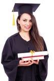 拿着书和垂度的毕业褂子的美丽的女学生 库存照片