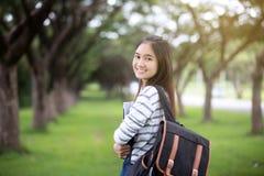 拿着书和微笑对照相机的美丽的亚裔女学生 免版税库存照片