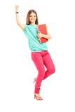 拿着书和打手势幸福的愉快的女学生 免版税图库摄影