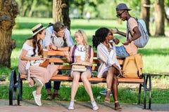 拿着书和纸杯的年轻不同种族的学生,当坐长凳和谈话在公园时 库存图片
