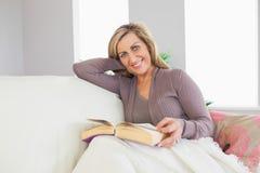 拿着书和说谎在沙发的微笑的妇女 库存照片