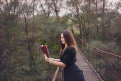 拿着书的一个少妇的秋天画象 免版税库存照片