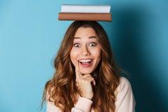 拿着书的一个愉快的爽快女孩的画象 免版税库存图片