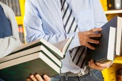 拿着书的图书管理员和学生在学院 库存图片