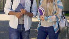 拿着书的女性和男学生,有交谈,学院朋友 股票视频