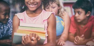 拿着书的微笑的女孩反对同学 免版税库存图片