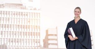 拿着书的微笑的法官画象在城市 免版税库存照片