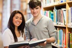 拿着书的愉快的学员 免版税库存图片