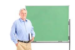 拿着书的成熟学校教师 库存图片