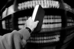 拿着书的手在图书馆里 免版税库存照片