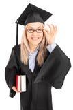 拿着书的毕业褂子的年轻女学生 库存图片