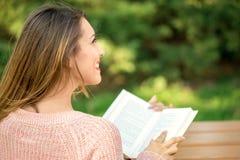 拿着书的美丽的女孩外面 免版税库存照片