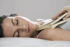 拿着书的美丽的妇女,当睡觉在床上时 免版税图库摄影