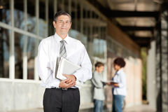拿着书的老师,当站立在校园里时 免版税库存照片