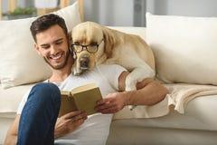 拿着书的英俊的人,当聪明的宠物读了它时 免版税库存照片