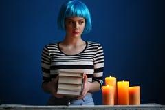 拿着书的蓝色假发的女孩 关闭 可能 库存照片
