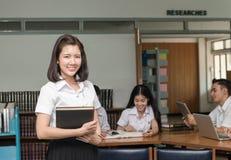 拿着书的逗人喜爱的微笑的学生画象在图书馆里 免版税图库摄影