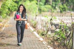 拿着书的年轻亚裔女学生,当走在pa时 免版税库存图片