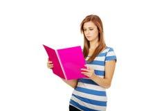 拿着书的年轻人微笑的少年妇女 免版税图库摄影