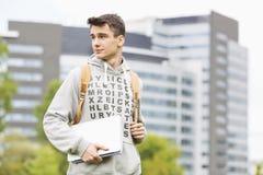 拿着书的年轻男性大学生在校园 免版税库存图片