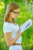 拿着书的年轻美丽的妇女画象  免版税库存照片