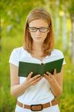 拿着书的年轻美丽的妇女画象  免版税库存图片