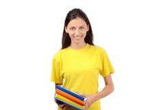 拿着书的黄色女衬衫的美丽的学生。 免版税库存图片