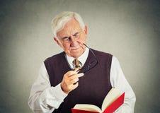 拿着书,玻璃的年长人有眼力问题 免版税库存图片