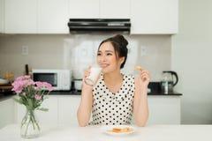拿着乳白玻璃叮咬曲奇饼的年轻亚裔妇女在她的厨房里 图库摄影