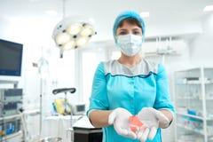 拿着乳腺癌了悟桃红色丝带的女性医生 免版税库存图片