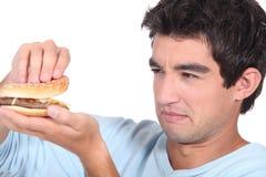 拿着乳酪汉堡的人 免版税库存照片