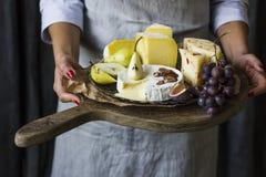 拿着乳酪的板材在木板的少妇 免版税库存照片