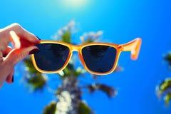 拿着五颜六色的太阳镜的女性手反对棕榈树和蓝色晴朗的天空 免版税图库摄影