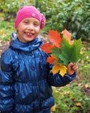 拿着五颜六色的槭树的一个小微笑的女孩的画象离开 库存图片