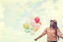 拿着五颜六色的气球和飞行在云彩天空背景的愉快的年轻红色头发妇女 库存图片