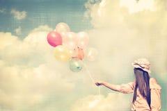 拿着五颜六色的气球和飞行在云彩天空背景的愉快的年轻红色头发妇女 图库摄影