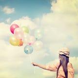 拿着五颜六色的气球和飞行在云彩天空背景的愉快的年轻红色头发妇女 免版税库存照片